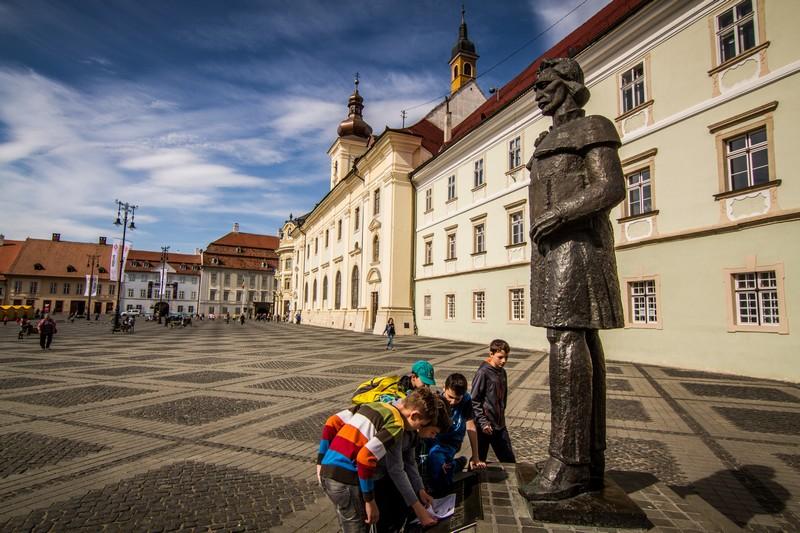 Elevi analizând statuia lui Gheorghe Lazăr din Piaţa Mare a Sibiului