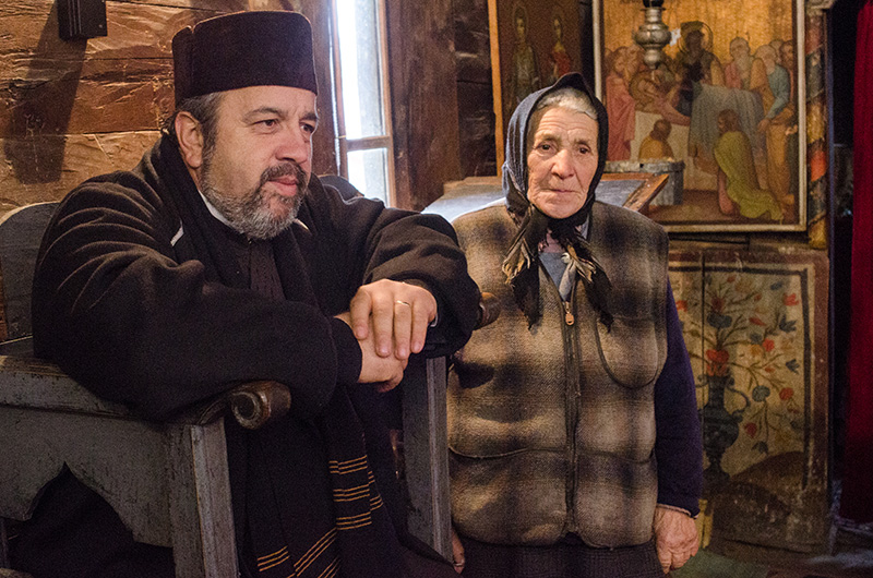 """Părintele Daniel Mazilu, alături de ajutorul său de nădejde, maica Aurica (88 de ani), """"șefa de la lumânări"""""""