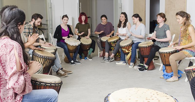 Elevii cursului de muzică africană sunt așezați în cerc, pentru o comunicare cât mai bună
